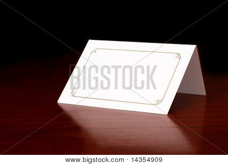 Blank card on dark timber table, with copy space.