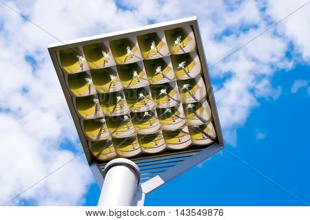 Outdoor faceted illumination reflector with ground reflection against the sky. Park or sports objects lighting equipment
