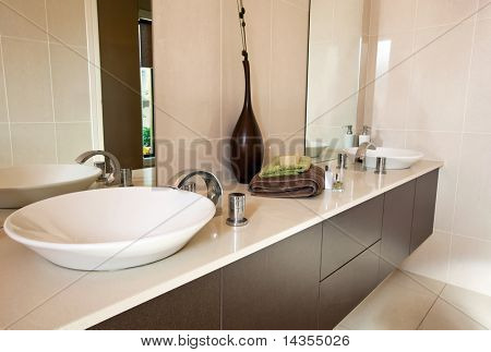 Modern bathroom, with double round basins.  Earthy warm tones.