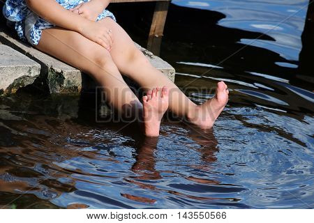 Young girl relaxes by the lake sitting on the edge of a wooden jetty , swing one's feet near the water surface. Sunny joyful summer day or evening concept