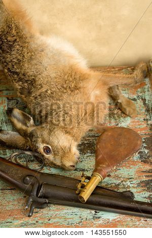 Old hunting scene with dead hare, rifle and leather gunpowder pouch