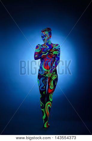 Erotica in ultraviolet light. Nude girl posing at camera