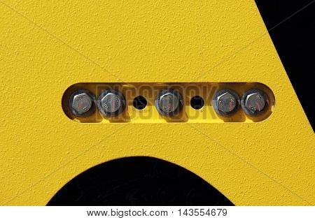 cap screws and holes in the yellow-black background - on the construction equipment compactor