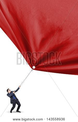 Young businessman wearing formal suit and pull a big red banner isolated on white background