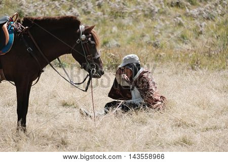 SAVANNA, INDONESIA - 12 AUG - Unidentified elderly local horses eating lunch in grassland with trusting horse in Savanna grassland at Mount Bromo, Indonesia on August 12, 2016