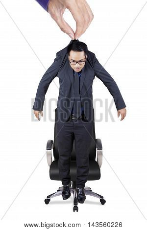 Hand lifting a businessman and put him on an office chair isolated on white background