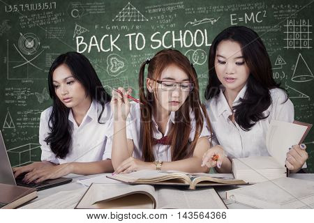 Portrait of three female students back to school and studying in the class while doing school assignment together