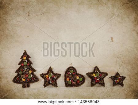 Handmade christmas tree with stars and heart tinkered with spicery on old wooden background.