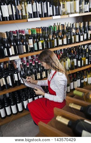 Saleswoman Taking Inventory In Wine Store
