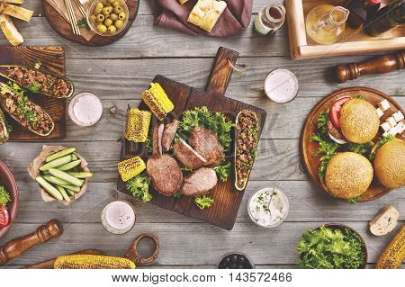 Outdoors Food Concept. On the wooden table different food steak burgers zucchini with meat bread salad bread snacks and beer top view