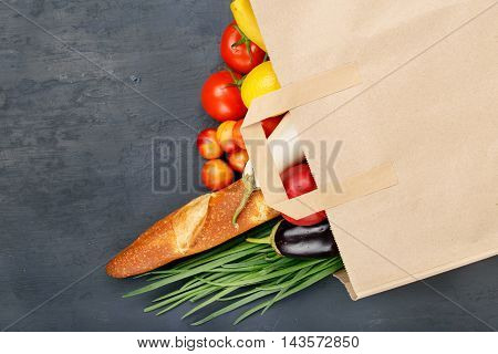 Full paper bag with different food on dark table with copy space top view. Food background