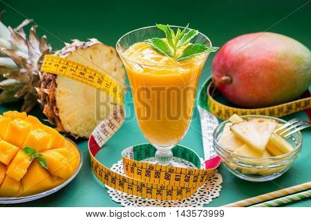 A glass of pineapple mango smoothie near ingredients, straws, centimeter on a green background. Pineapple mango smoothie ingredients and centimeter. Horizontal. Daylight.