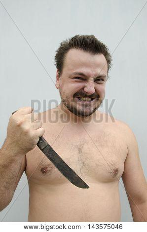 Bearded man holding rusty knife. Horror concept