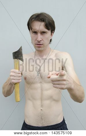 Young man holding axe on gray background