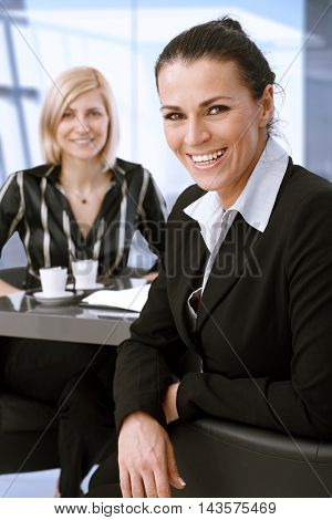 Middle-aged caucasian businesswoman on meeting sitting at table turning back laughing.