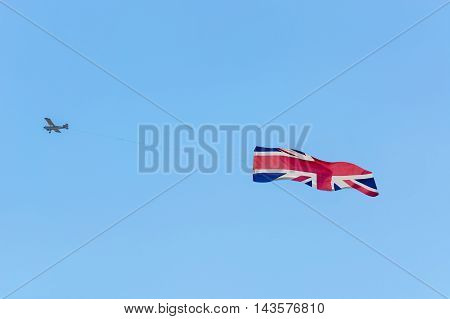 Banner towing small engine aircraft towing banners for advertising. Here the flag of Great Britain.