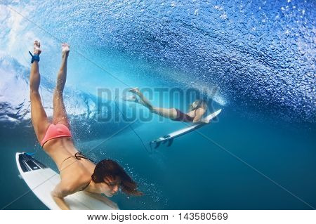 Active girls in bikini in action - surfers with surf board dive underwater under breaking big ocean wave. Family lifestyle people water sport adventure camp beach extreme swim on summer vacation