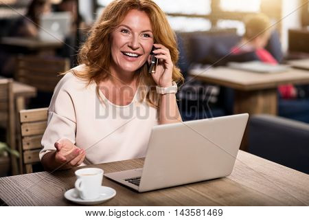 Busy lady. Cheerful and positive woman sitting at the table with cup of coffee and a laptop in a cafe and talking on her smart phone while gesturing