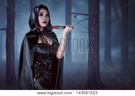 Asian Witch Woman Holding Knife In Forest