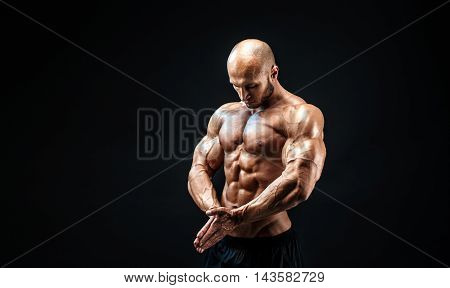Close up on perfect abs. Strong bodybuilder with six pack.Strong bodybuilder man with perfect abs, shoulders, biceps, triceps and chest, personal fitness trainer flexing his muscles.