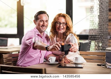 Photo together. Cheerful man and woman making selfie photos with the help of smart phone and selfie stick