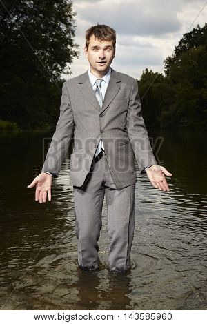 Crazy businessman in suit relaxing in river