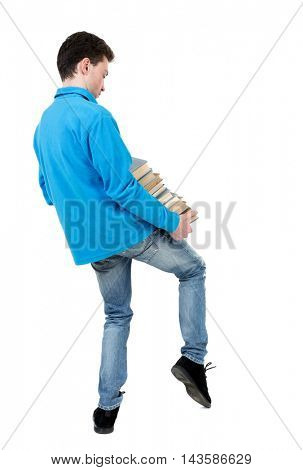 A man carries a heavy pile of books. back view. Rear view people collection.  backside view of person.  Isolated over white background. The curly-haired student in a blue sweater is trying to keep