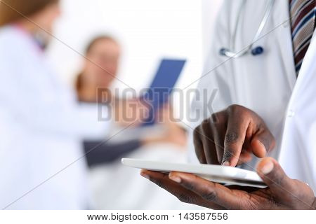 Black male doctor hand point with finger in digital tablet pc touch screen with patient lying in bad in background. Professional equipment therapeutist ward round search opportunities concept