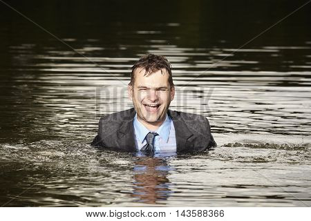 Crazy businessman in suit relaxing in water when swimming