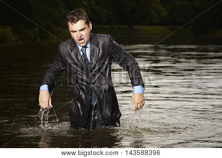 Crazy businessman in suit leaving water in summer time