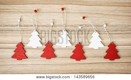 Red and white decorative little christmas trees on the wooden background. Symbolic objects. Yuletide theme.