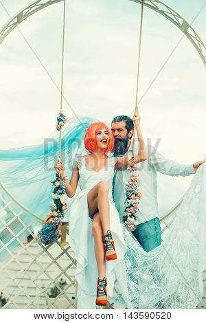 young couple of woman with orange hair and pretty face in white wedding dress red shoes and blue bride veil with handsome bearded man with violet beard on sky background near floral swing