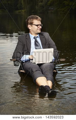 Crazy businessman in suit relaxing on folding chair with notebook