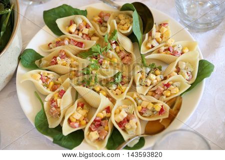 pasta shells filled with corn, sausage, and pickles mayonaise salad