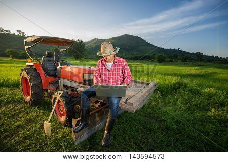 Young Farmer recorded growth of productivity sitting on a tractor in the background a rice paddy fields mountains and sky.