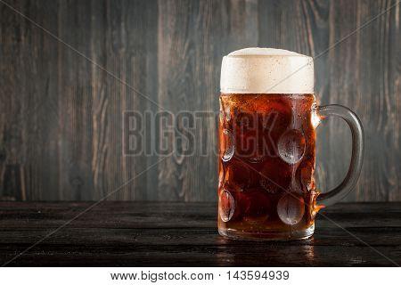 Mug of dark beer on wooden background
