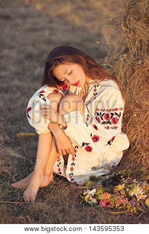Slav teen girl at yellow meadow sitting in national ukrainian clothing with wreath of flowers. Sunset warm weather