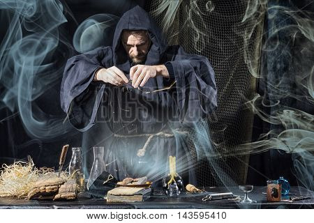 Halloween. The Medieval Alchemist Holds Magic Ritual At The Table In His Laboratory Smoke In The Bac