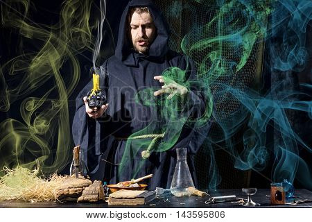 Halloween. The Medieval Alchemist In His Hand A Skull With Candles And Holds Magic Ritual At The Tab