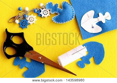Felt blue anchor keychain, scissors, white thread, pin, paper pattern, blue felt sheet on yellow background with empty space for text. Handicrafts and sewing crafts concept. Bright summer background