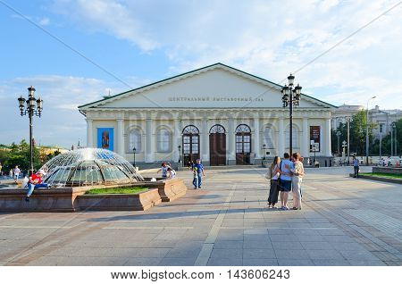 MOSCOW RUSSIA - JULY 23 2016: Unidentified people walk on Manezhnaya Square near Central Exhibition Hall Manege Moscow Russia