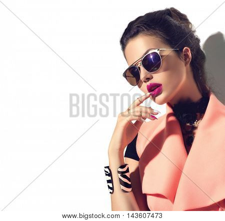 Beauty Fashion model girl with brown hair wearing stylish sunglasses. Sexy woman portrait with perfect makeup and manicure, trendy accessories and fashion wear. Beauty trends. Isolated on white
