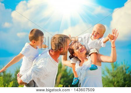 Happy Young Family with two children walking on summer field, having fun together. Healthy mother, father and little sons enjoying nature outdoors. Healthy Smiling Dad, Mom and kids over blue sky