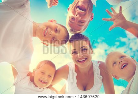 Happy Young Big Family with three children having fun together. Healthy mother, father and little sons enjoying nature outdoors. Huddle, circle, hugging. Healthy Smiling Dad, Mom, kids over blue sky