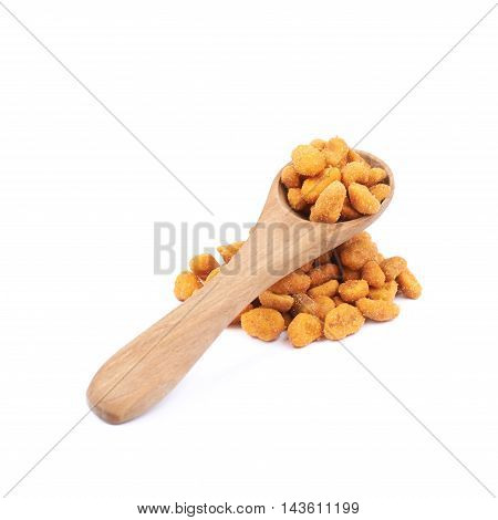 Pile of breaded peanuts with the wooden spoon over it, composition isolated over the white background