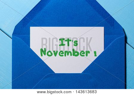 It's November - sign on paper at open blue post envelope. Autumn time concept.