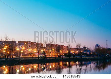 The View Of Urban Residential Area Overlooks To City Lake And Park In Evening Illumination, Reflecting In Water Surface. Early Spring, Gomel Belarus