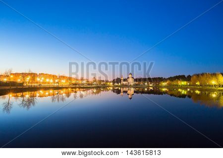 Evening View Of Alexander Nevsky Orthodox Temple Church Behind City Lake. Evening Illumination Of Residential Area And Park Reflecting In Water Surface. The Early Spring In Gomel Homiel Belarus