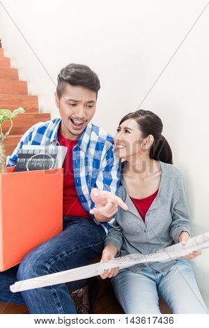 Asian couple, woman and man, on moving day  planning arrangement of their new apartment with floor plan