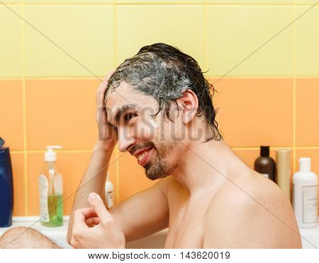 The Young Happy Man is Washing in the Bathroom